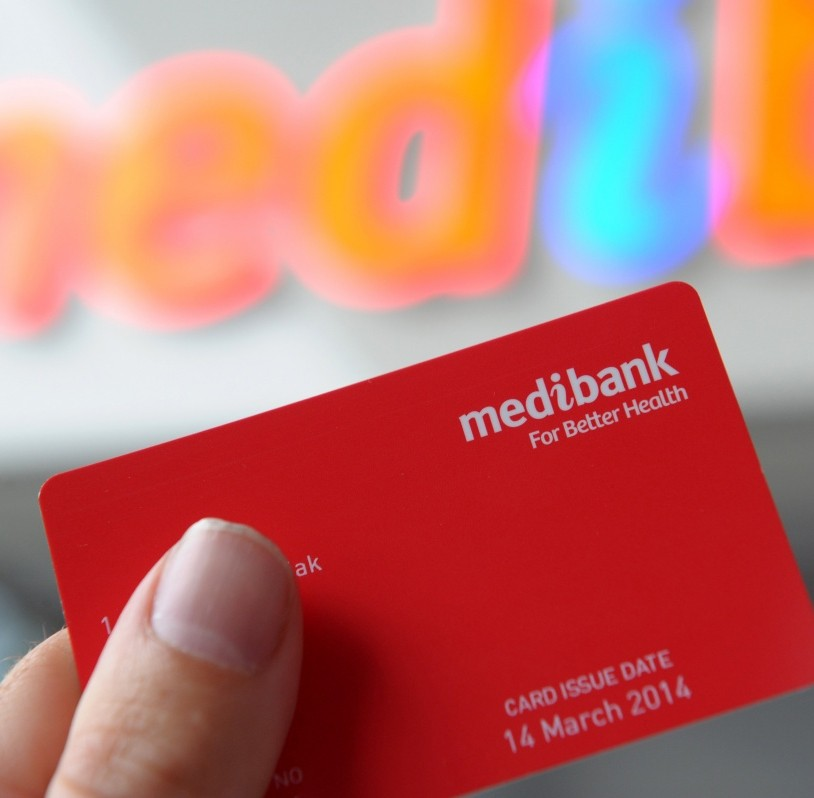 A Medibank health insurance card being held up in front of a Medibank store.